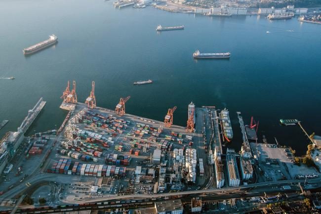 © Bloomberg. Containers sit stacked at Vancouver Harbour in this aerial photograph taken above Vancouver, British Columbia, Canada, on Thursday, Sept. 6, 2018. The U.S. and Canada continued to look for ways to bridge their differences as talks resumed to update the North American Free Trade Agreement, with Ottawa insisting it won