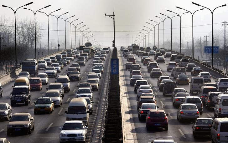 © Reuters. FILE PHOTO: Cars drive along a main road in central Beijing