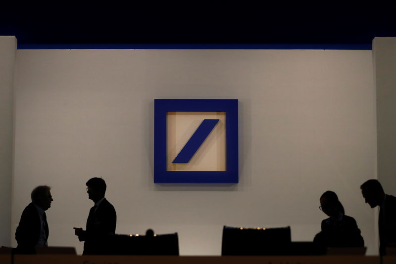 © Reuters. FILE PHOTO: People are silhouetted next to the Deutsche Bank