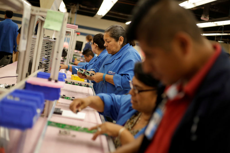 © Reuters. FILE PHOTO: Employees of NDP Technology, a private company specialised in PCB (Printed Circuit Board) assembly for different industries, works on a printed circuit board in Ciudad Juarez