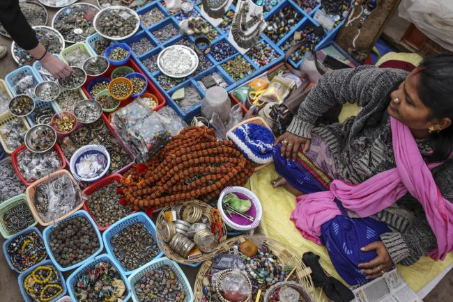 © Bloomberg. A vendor sells jewelry and accessories at Dashasumedh ghat on the banks of the Ganges river in Varanasi, Uttar Pradesh, India, on Friday, Dec. 9, 2016. India is scheduled to release Consumer Price Index (CPI) figures for November on Dec. 13.