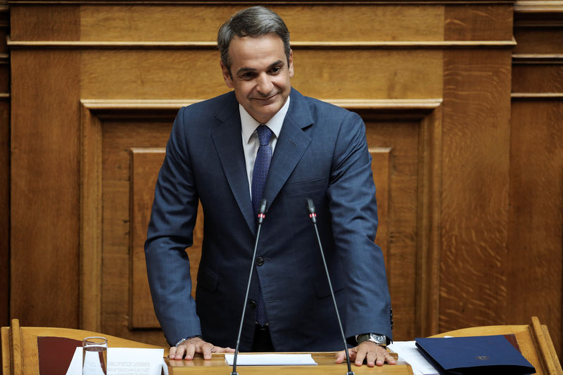 © Reuters. Greek PM Mitsotakis smiles as he addresses lawmakers during a parliamentary session in Athens