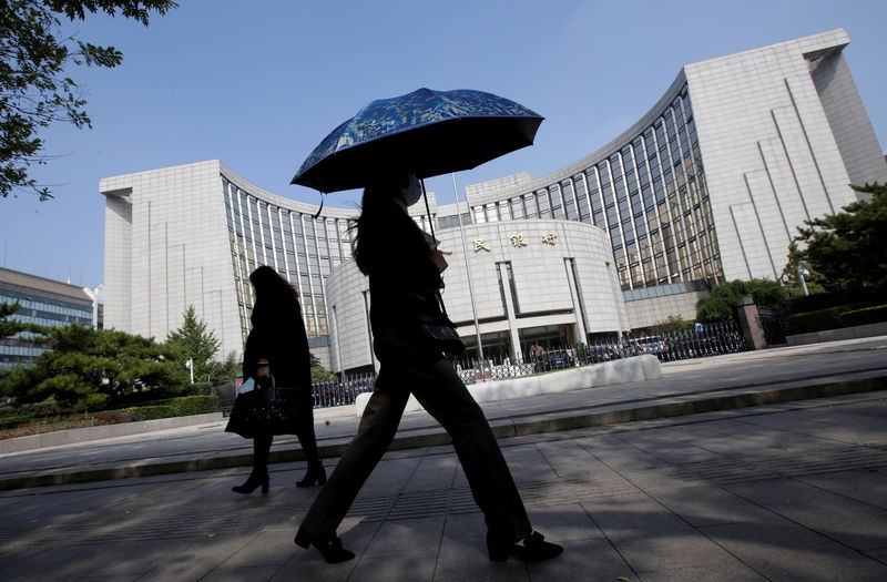 © Reuters. FILE PHOTO: People walk past the headquarters of the PBOC, the central bank, in Beijing