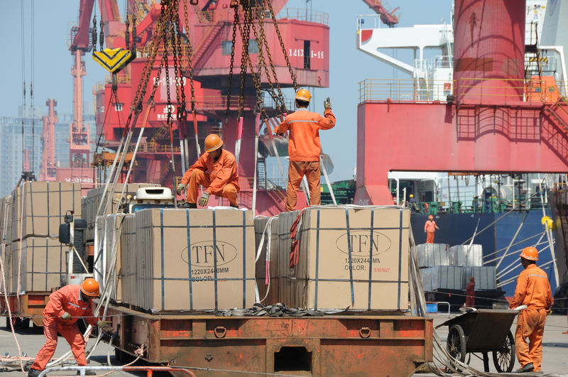 © Reuters. Workers load goods for export onto a crane at a port in Lianyungang