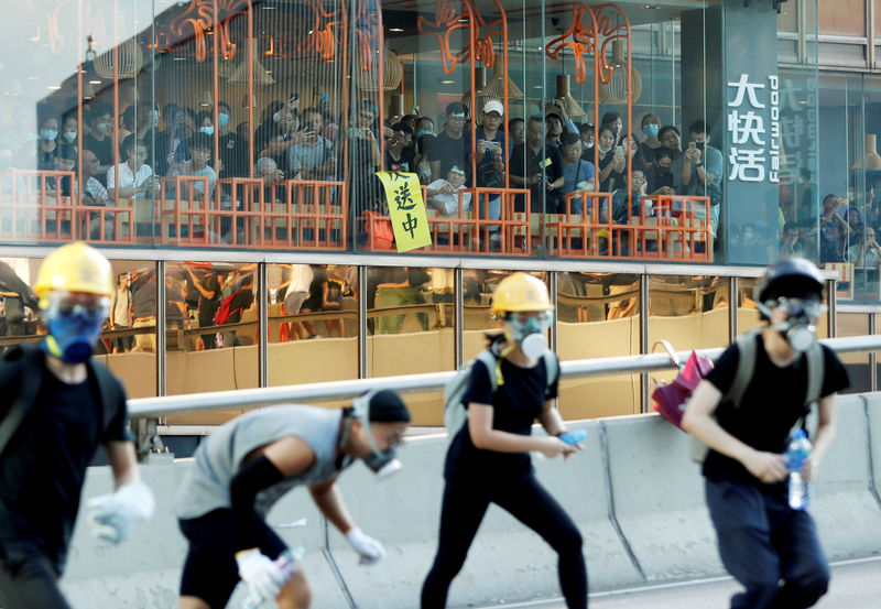© Reuters. FILE PHOTO: People inside a restaurant watch as protesters attend a demonstration in support of the city-wide strike and to call for democratic reforms outside Central Government Complex in Hong Kong