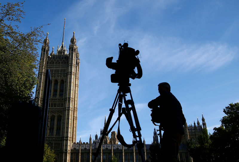 © Reuters. A member of the media sets up a TV camera in front of the Houses of the Parliament in London