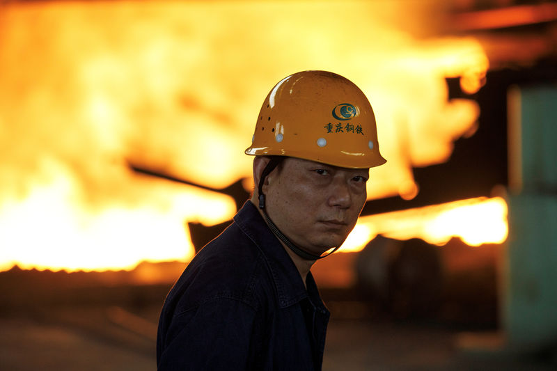 © Reuters. FILE PHOTO: Worker looks on in front of a blast furnace at the Chongqing Iron and Steel plant in Changshou