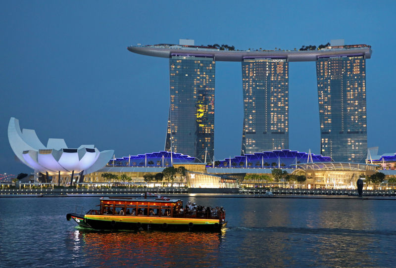 © Reuters. FILE PHOTO: A tourist bum boat passes by the Marina Bay Sands hotel in Singapore