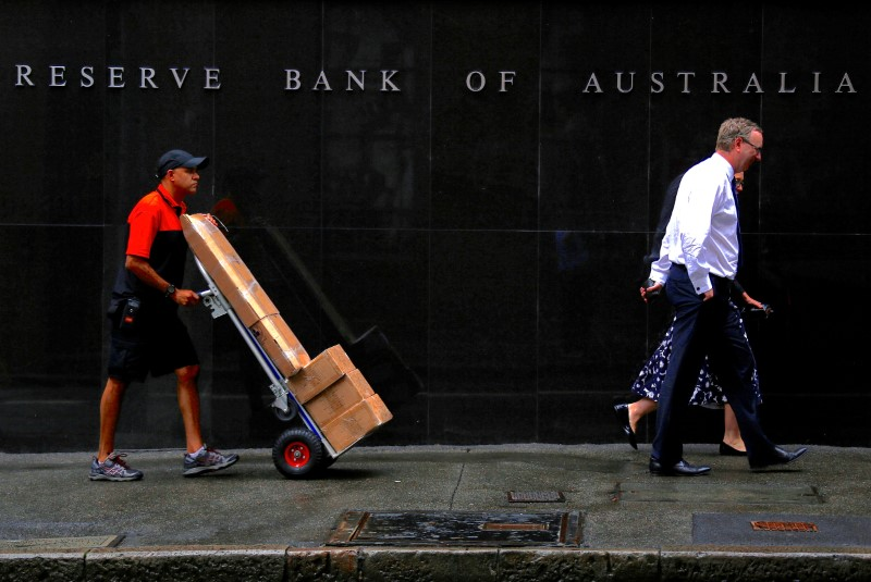 © Reuters. A worker pushing a trolley walks with pedestrians past the Reserve Bank of Australia (RBA) head office in central Sydney