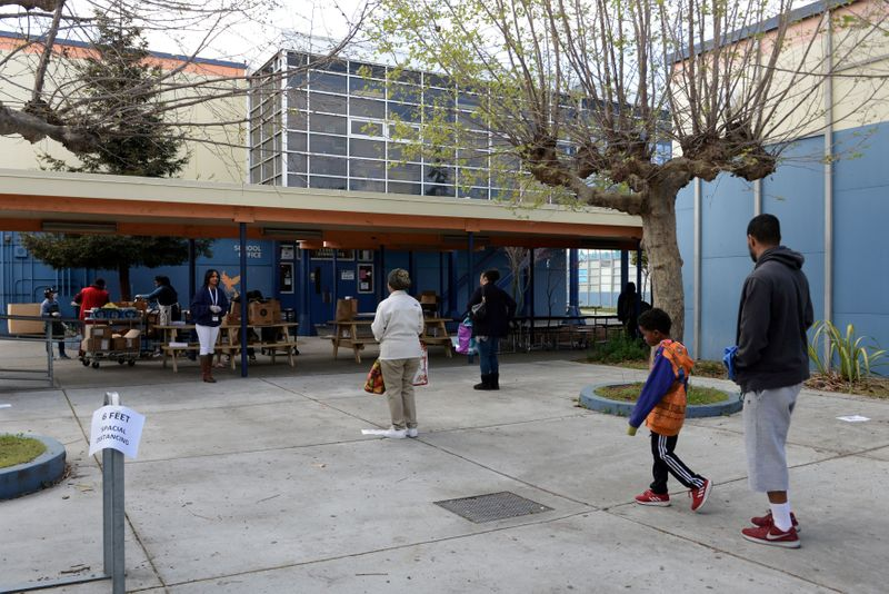 """© Reuters. FILE PHOTO: Families practice social distancing while waiting in line at West Oakland Middle school to pick up """"grab and go"""" meals during the Oakland Unified School District shutdown in Oakland"""