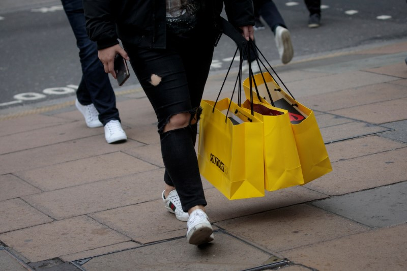 © Reuters. FILE PHOTO: Shoppers carry bags from a department store in Oxford Street, in London