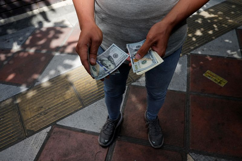 © Reuters. An unauthorised seller counts U.S. dollars at Ferdowsi square in Tehran