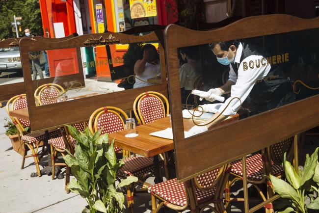 © Bloomberg. A worker wearing a protective mask and gloves sets a table outside a restaurant in New York. Photographer: Angus Mordant/Bloomberg