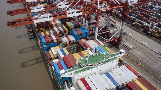 © Bloomberg. A vessel loaded with shipping containers is docked at the Yangshan Deepwater Port in this aerial photograph taken in Shanghai, China, on Sunday, July 12, 2020. U.S. President Donald Trump said Friday a phase two trade deal with China isn