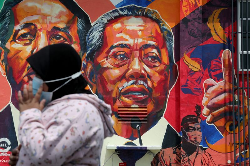 © Reuters. A woman passes by a mural depicting Malaysia's Prime Minister Muhyiddin Yassin in Kuala Lumpur
