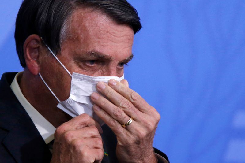 © Reuters. FILE PHOTO: Brazil's President Jair Bolsonaro looks on as he adjusts his protective face mask during a ceremony launching a program to expand access to credit at the Planalto Palace in Brasilia