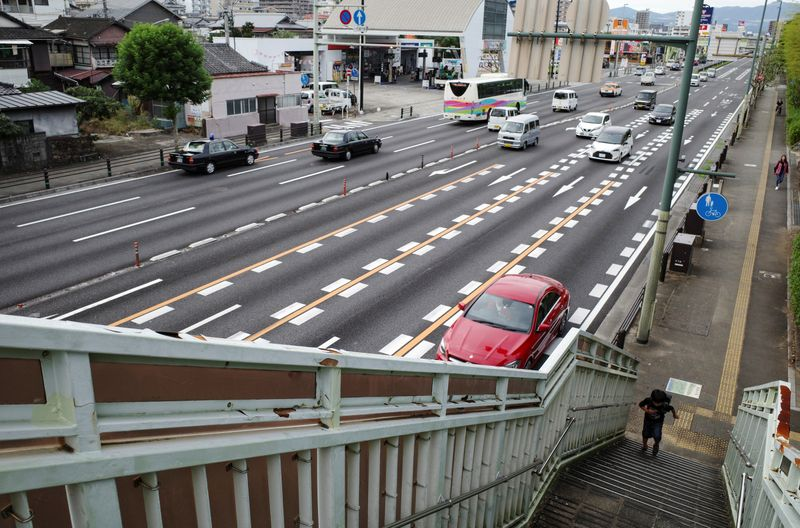 © Reuters. FILE PHOTO:  A schoolboy walks up the overhead bridge along a traffic junction in Beppu