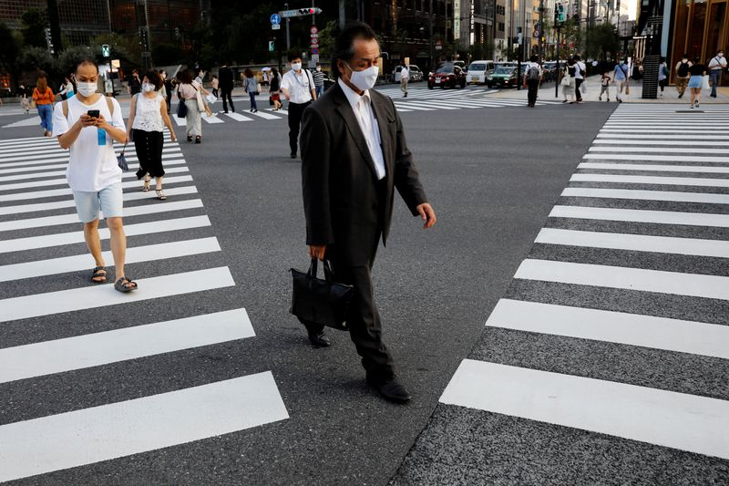 © Reuters. FILE PHOTO: People wearing protective masks make their way at a business district in Tokyo